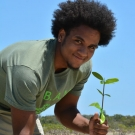 Forest Heights Academy 12th grader is excited to be on a fieldtrip planting his mangrove propagules.