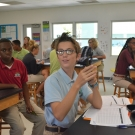 Forest Heights Academy student holds up his three mangrove seedlings that he is going to plant during today's class.