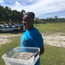 A brave student from Abaco Central High School fills the plant flat with mangrove mud. It's a dirty job, but she was happy to do it.