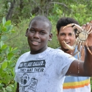 1.	A student picks up a crab climbing in the roots of the mangroves.