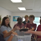 Students at Forest Heights Academy hold a sea cucumber. Some students are holding this organisms for the first time.