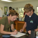 Ryann Rossi, PhD Candidate at North Carolina State University helps a student at Forest Heights Academy to isolate a piece of his diseased mangrove leaf.