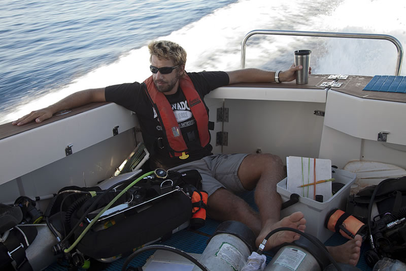 Anderson Mayfield wakes up with a cup of coffee during a long transit out to our first dive of the day.