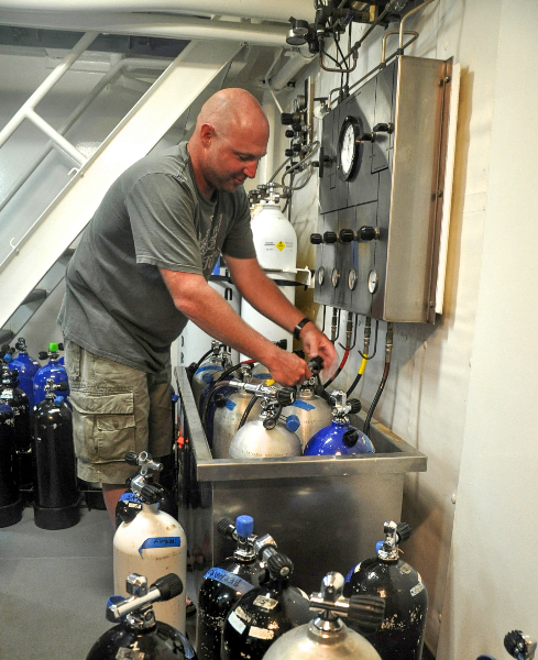 Timothy Payne II prepares tanks for a dive.