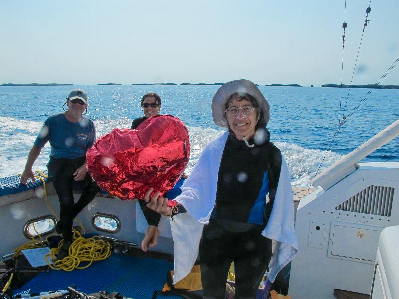 Judy Lang holds up a heart shaped ballon.