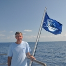Phil Renaud stand next to an earth flag on the Golden Shadow.