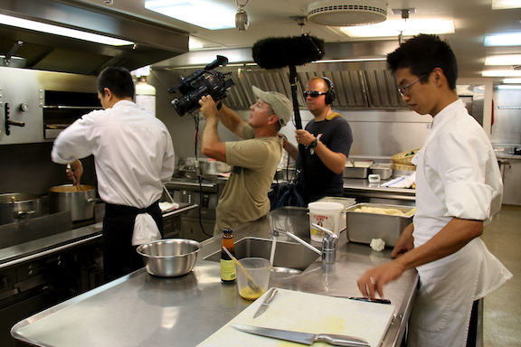 Doug Allan and Curig Huws filming the chefs busily preparing supper in the galley for the Golden Shadow Ship Tour video.