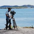 Cameraman Doug Allan shooting fishing boats at the dock in Newfoundland