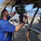 Cameraman James Ball filming on the beach in Honduras.
