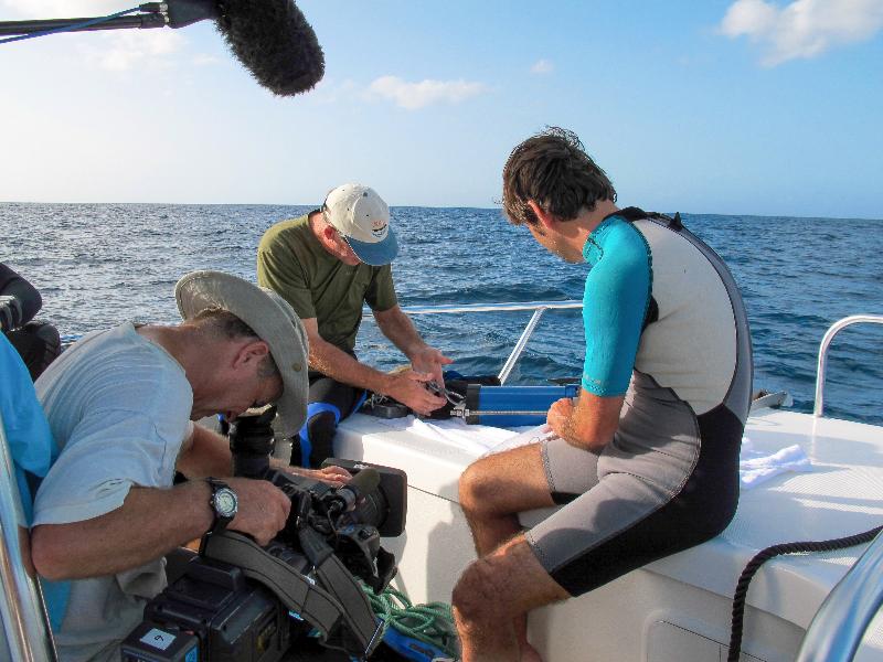 CAPT Phil Renaud and Dr. Sam Purkis explain scientific equipment to the film crew.