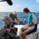 CAPT Phil Renaud and Dr. Sam Purkis explain scientific equipment to the film crew.