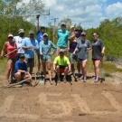 Alumni from Louisiana State University volunteer during their vacation to help remove old stumps and level soil at the JAMIN mangrove restoration site.