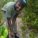 Tenth grade student from Holland High School pauses for a photo before she plants her mangrove propagule.