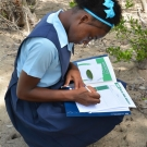 A student answers questions on her activity worksheet while on a field trip to a mangrove forest.
