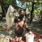 A fisherman shows off his prize catch: a large snapper.
