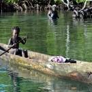 A young child paddles around in his dugout canoe.