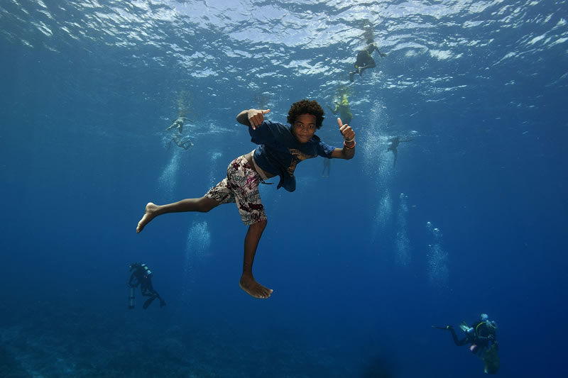 Local children free-diving to have their photos taken by scientists who are scuba diving.