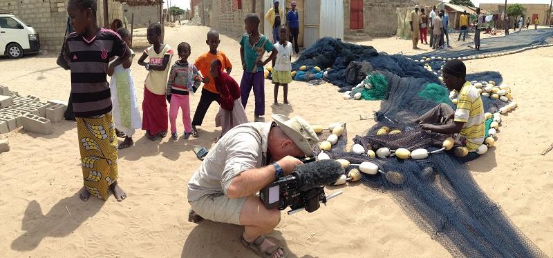 Filming a fishermen repairing his net.