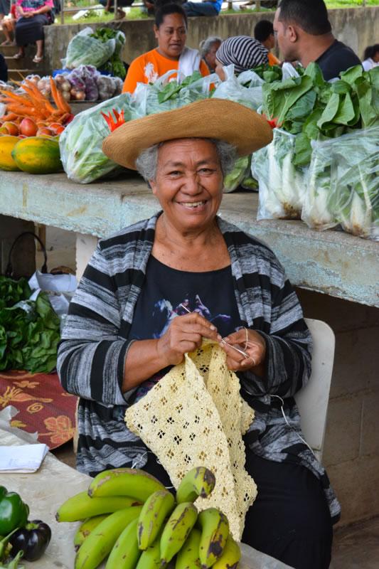 A woman weaving dried pandanus leaves at the farmer's market
