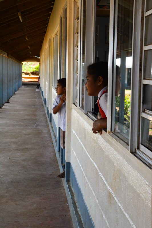 Students at GPS Liviela peaking at the courtyard to see what was going on.