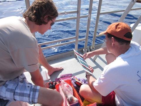 Alan Bright (left) explains coral survey equipment to Mike Trimble (right), the Navassa Mission's CREW participant.
