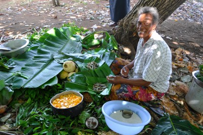 A Tongan woman is preparing food for the umu. To the left, notice the papaya and coconut milk dish.