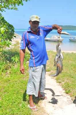 A Tongan fisherman holds up his catch from the morning.