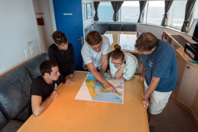 KSLOF Scientists review great barrier reef zoning map aboard golden shadow.