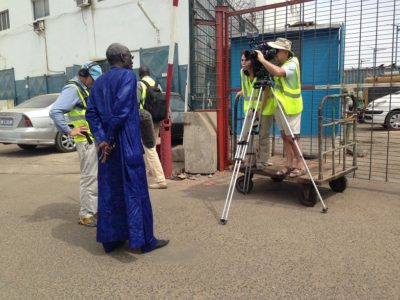 Cameraman Doug Allan filming fishermen selling their catch in the Port of Dakar