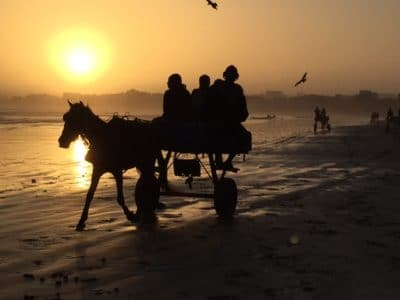Fishermen gather on the beach at dawn to prepare for a day of fishing