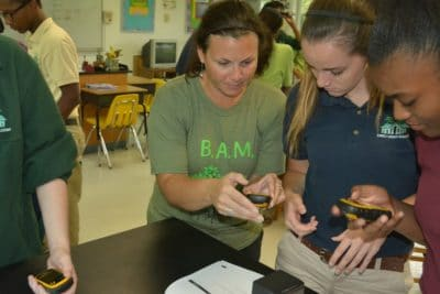Prior to the fieldtrip, Amy Heemsoth, Director of Education teaches students how to use a GPS device.