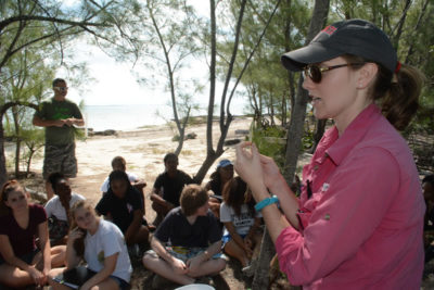 Ryann explains to students how to identify diseased red mangrove leafs at field trip site.