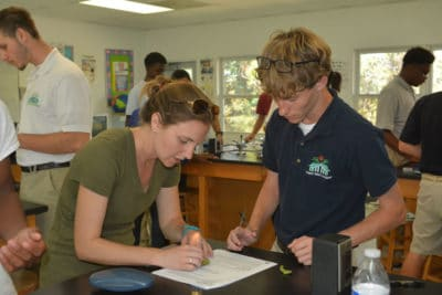 Ryann Rossi helps student at Forest Heights Academy to remove a small diseased portion of his mangrove leaf.