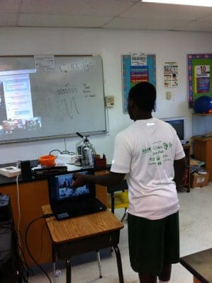 Forest Heights student discusses the fungi on his agar plate with Ryann who is on a video call with the class.