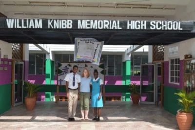 Intern Maggie Dillon stands out front of William Knibb High School in Jamaica with two students after a guided tour of the school.